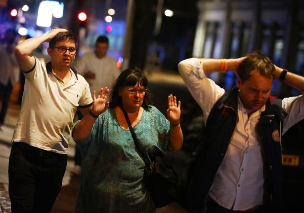 People-leave-the-area-with-their-hands-up-after-an-incident-near-London-Bridge-in-London